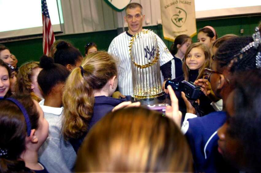 New York Yankees' manager, Joe Girardi, with his daughter, Serena Girardi, right, and the students of Convent of the Sacred Heart, admire the 2009 World Series campionship trophy, on January 26, 2010 at the school's celebration for the Yankees.