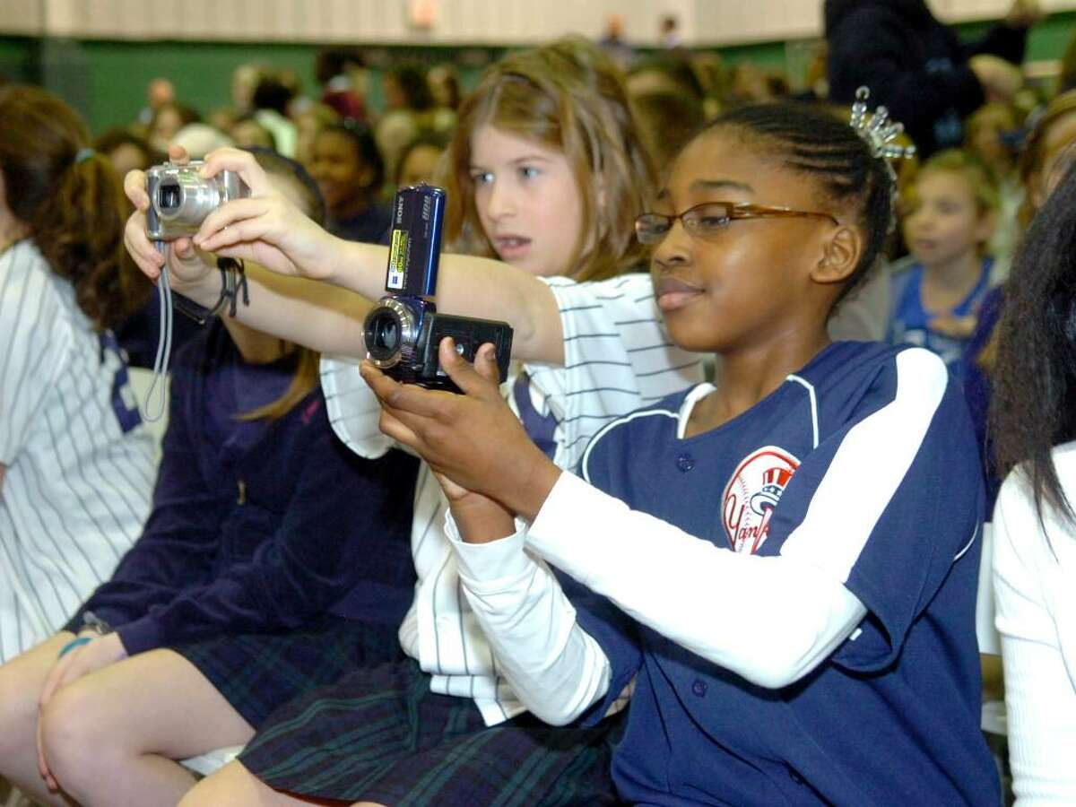 Convent of the Sacred Heart students Kathryn Allyn, and Jade Brown, both 11, take pictures of the Yankees' trophy during the school's celebration of the Yankees' 2009 World Series Championship.