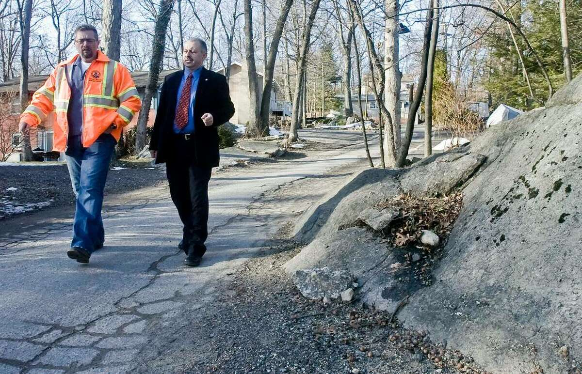 Antonio Iadarola, Director of Public Works along with city engineer Farid Khouri, walk along Cornell Road. Well traveled narrow roads with rock ledge close to the roadsides would make and construction disruption very difficult for the homeowners. Residents wanted public water and sewer but bailed out when they realized how expensive it would be Thursday, Jan. 21, 2010