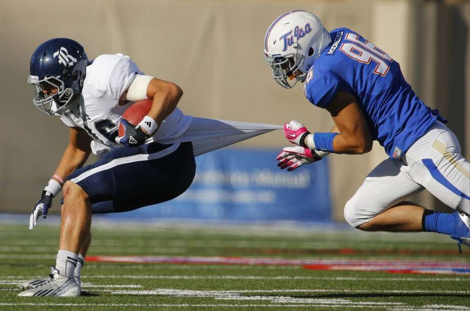 Rice's Taylor McHargue, left, is pulled down by Tulsa's Dalton Rodriguez during the second half of an NCAA college football game Oct. 5, 2013, at Chapman Stadium in Tulsa, Okla. (AP Photo/Tulsa World, Tom Gilbert) Photo: Tom Gilbert, Associated Press