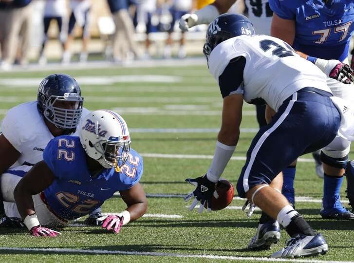 Rice's Paul Porras, right, recovers a fumble by Tulsa's Trey Watts (22) during the first half an NCA