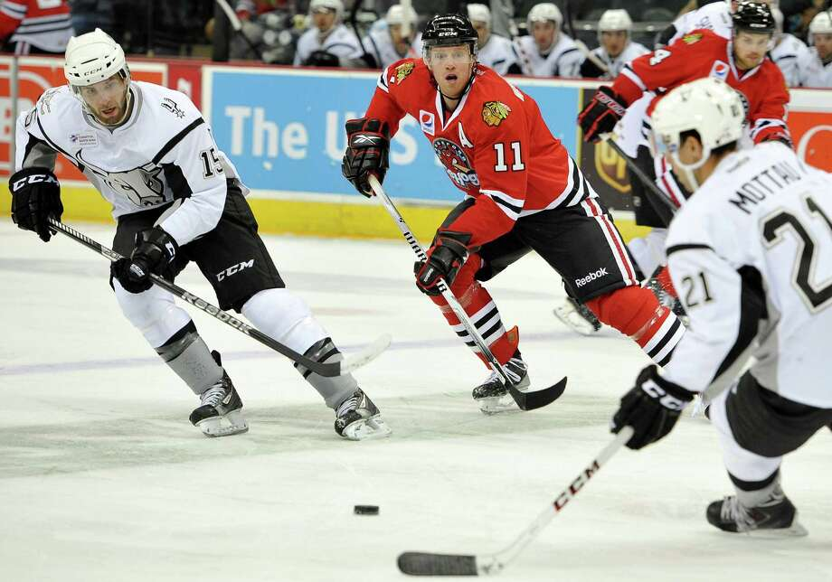 San Antonio Rampage's Eric Selleck, left, passes to teammate Mike Mottau, right, in front of Rockford IceHogs' Brad Winchester during the first period of an AHL hockey game, Saturday, Oct. 5, 2013, in San Antonio. Photo: Darren Abate, Darren Abate/M3D14.com / Darren Abate/DA Media, LLC