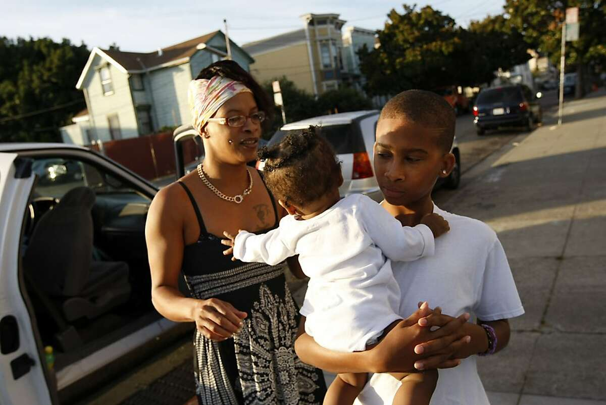 Carjuan Thomas, 13, holds his baby sister Zion Bradford while their mom Dameka Bradford looks on as they visit with friends in front of Upperkutz barber shop in West Oakland, California Wednesday October 2, 2013.