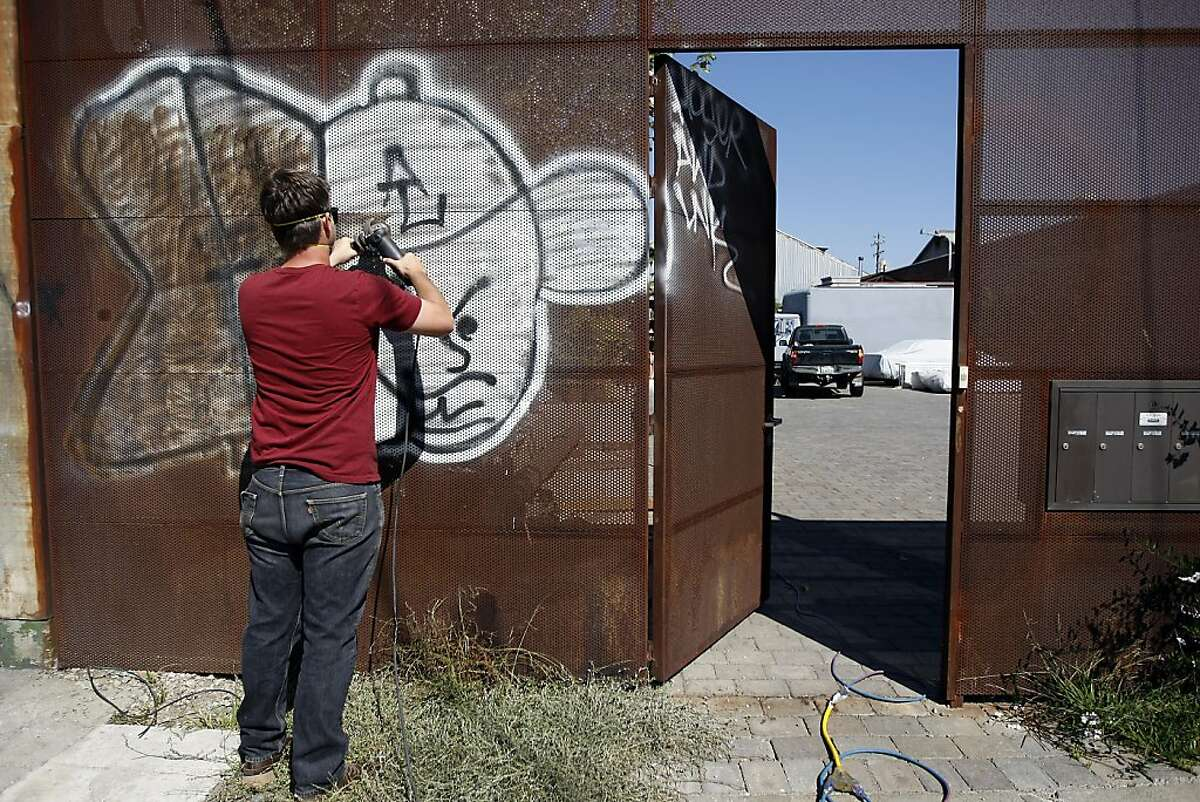 Landon Rose uses a grinder as he tries to remove graffiti from the front gate of his workplace, Berland Design, an architectural steel and custom furniture shop in West Oakland, California Wednesday October 2, 2013.