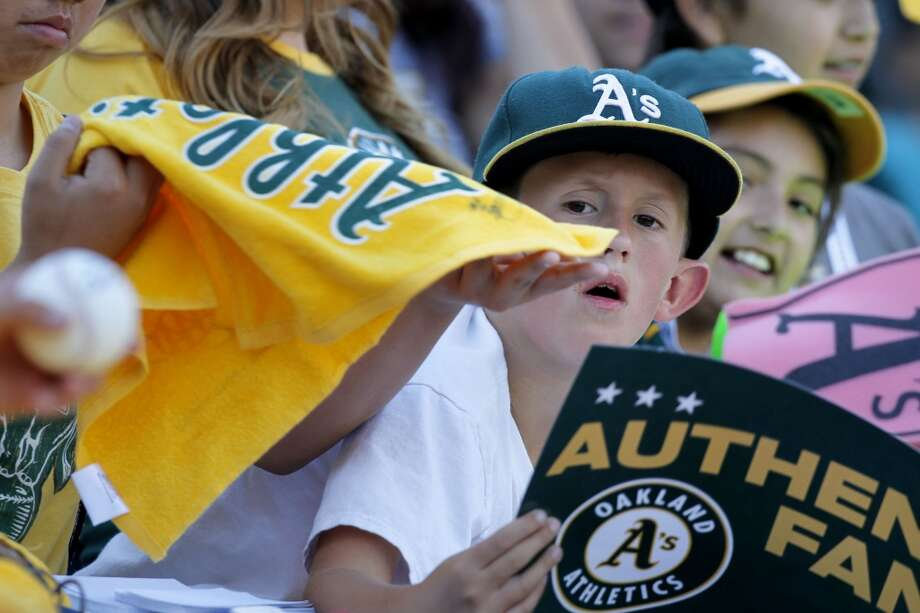 Fans try for autographs before the start, on Saturday Oct. 5, 2013, in Oakland, Calif. at O.co Coliseum, as the Oakland Athletics prepare to take on the Detroit Tigers in game two of the MLB American League Division Series. Photo: Michael Macor, The Chronicle