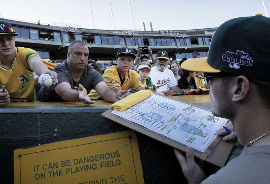 A's Josh Donaldson, (20) signs autographs before the game, on Saturday Oct. 5, 2013, in Oakland, Calif. at O.co Coliseum, as the Oakland Athletics prepare take on the Detroit Tigers in game two of the MLB American League Division Series. Photo: Michael Macor, The Chronicle