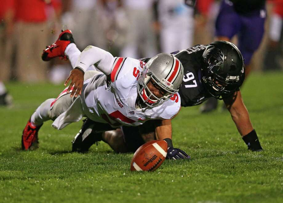 EVANSTON, IL - OCTOBER 05: Braxton Miller #5 of the Ohio State Buckeyes tires to recover his own fumble after being tackled by Tyler Scott #97 of the Northwestern Wildcats at Ryan Field on October 5, 2013 in Evanston, Illinois. (Photo by Jonathan Daniel/Getty Images) ORG XMIT: 182045477 Photo: Jonathan Daniel / 2013 Getty Images
