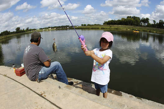 Hey, Chuck, there are fish in the river! Nelly Sanchez holds up her fishing pole to reveal a small perch on her line as she and older brother Isiah fish along the Mission Reach.