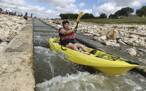 Kayaker Elsa Perez navigates the chute near Padre Park as people celebrate the completion and grand opening of the Mission Reach Ecosystem Restoration and Recreation Project along the San Antonio River. Photo: Photos By Kin Man Hui / San Antonio Express-News