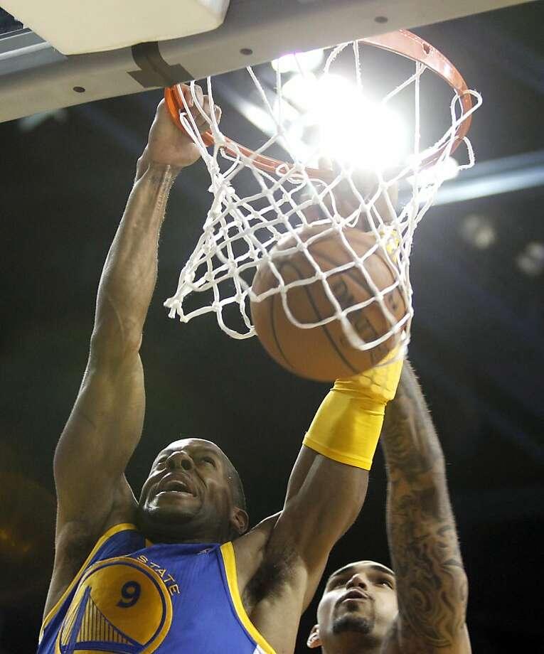 Warriors guard Andre Iguodala (left) goes for the dunk against the Lakers' Robert Sacre. Photo: Alex Gallardo, Associated Press