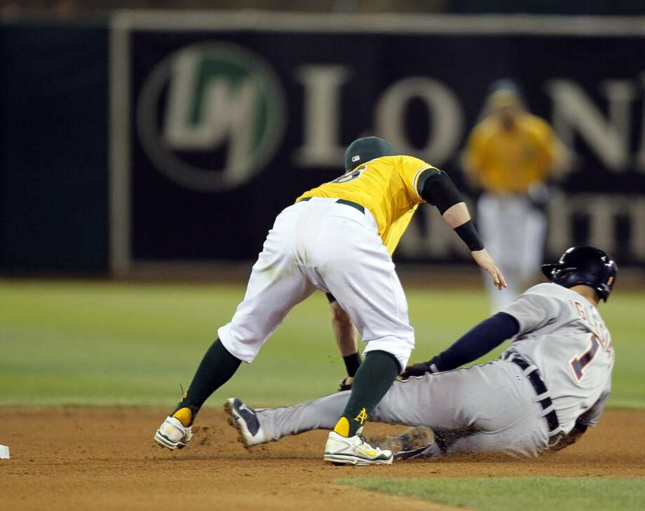 Eric Sogard tags out Jose Iglesias as he tried to steal on a strike out in the fifth inning. The Oakland Athletics played the Detroit Tigers in Game 2 of the American League Division Series at O.co Coliseum in Oakland, Calif., on Saturday, October 5, 2013. Photo: Michael Macor, The Chronicle