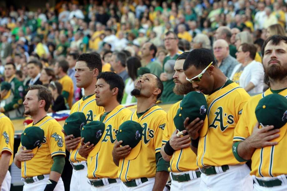 The Oakland Athletics players listen to the national anthem before the start of game 2. The Oakland Athletics played the Detroit Tigers in Game 2 of the American League Division Series at O.co Coliseum in Oakland, Calif., on Saturday, October 5, 2013. Photo: Michael Macor, The Chronicle