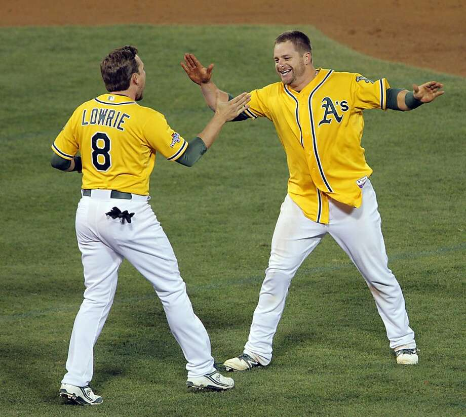 Jed Lowrie runs to hug Stephen Vogt after Vogt hit the game-winning hit to score Yoenis Cespedes in the bottom of the ninth inning. The Oakland Athletics played the Detroit Tigers in Game 2 of the American League Division Series at O.co Coliseum in Oakland, Calif., on Saturday, October 5, 2013. Photo: Carlos Avila Gonzalez, The Chronicle
