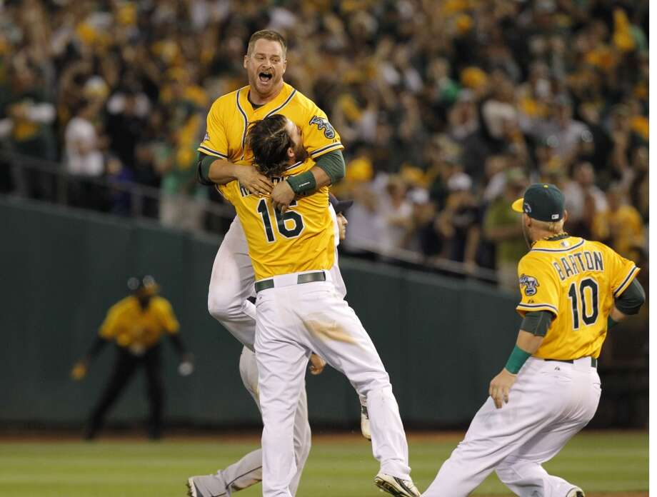 A's catcher Stephen Vogt, (21) jumps into the arms of Josh Reddick, (16) in celebration with a walk off win with the bases loaded on Saturday Oct. 5, 2013, in Oakland, Calif. at O.co Coliseum, as the Oakland Athletics beat the Detroit Tigers 1-0 n game two of the MLB American League Division Series. Photo: The Chronicle