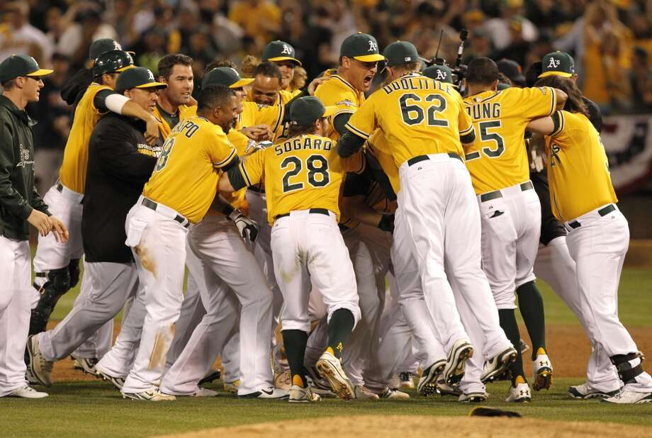 Teammates sarm A's catcher Stephen Vogt, (21) after his walk off win with the bases loaded on Saturday Oct. 5, 2013, in Oakland, Calif. at O.co Coliseum, as the Oakland Athletics beat the Detroit Tigers 1-0 n game two of the MLB American League Division Series. Photo: The Chronicle