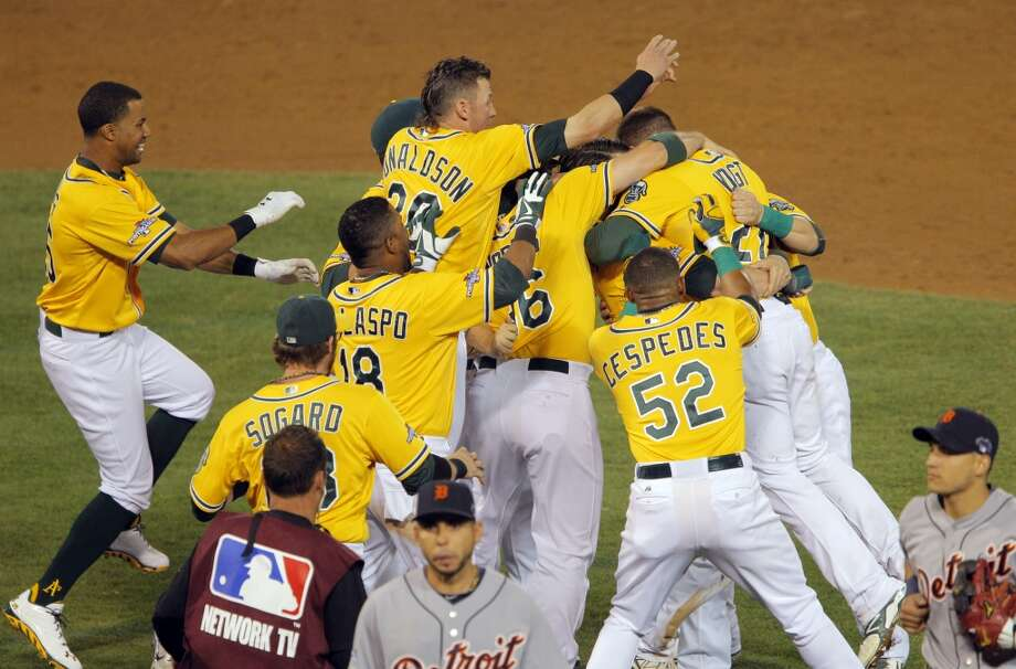 Stephen Vogt is mobbed by teammates after he hit the game-winning hit to score Yoenis Cespedes in the bottom of the ninth inning. The Oakland Athletics played the Detroit Tigers in Game 2 of the American League Division Series at O.co Coliseum in Oakland, Calif., on Saturday, October 5, 2013. Photo: The Chronicle