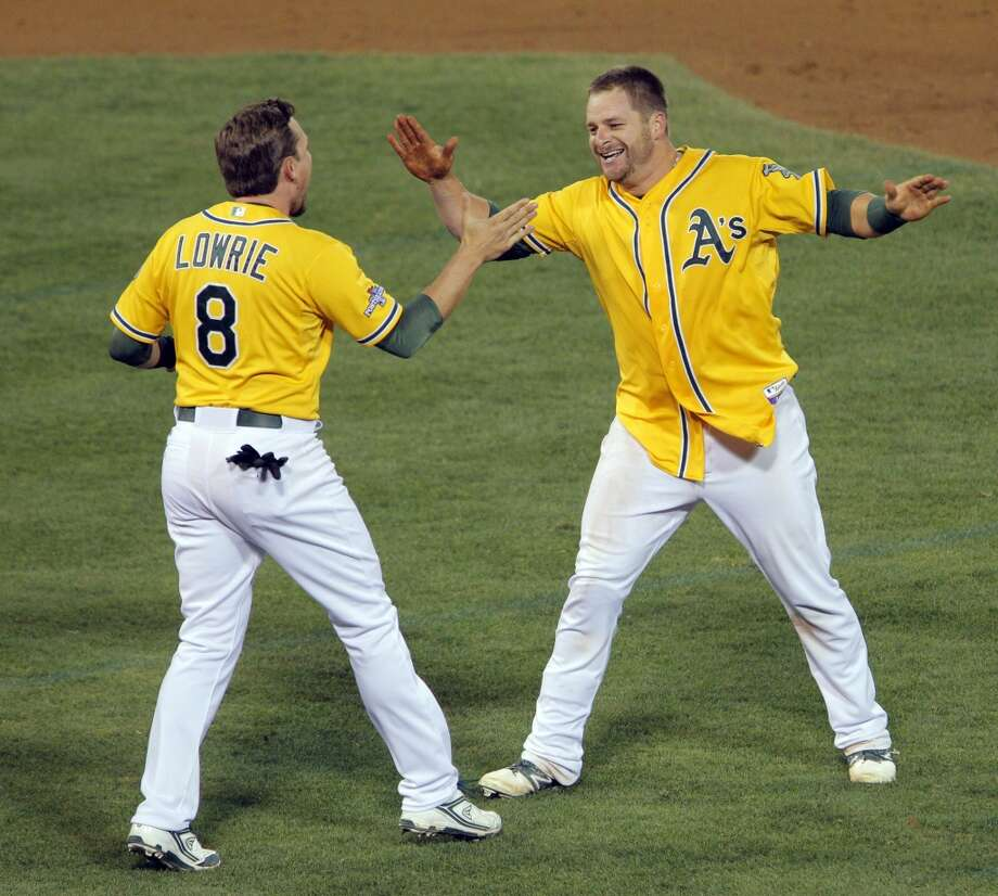 Jed Lowrie runs to hug Stephen Vogt after Vogt hit the game-winning hit to score Yoenis Cespedes in the bottom of the ninth inning. The Oakland Athletics played the Detroit Tigers in Game 2 of the American League Division Series at O.co Coliseum in Oakland, Calif., on Saturday, October 5, 2013. Photo: The Chronicle