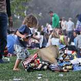 Two year old Judah Kai Leaper-Zakzouk helps his father Kal Zakzouk (left) clean up recycling at the Hardly Strictly Bluegrass Festival in Golden Gate Park, in San Francisco, Ca, on Saturday, Oct. 5, 2013.