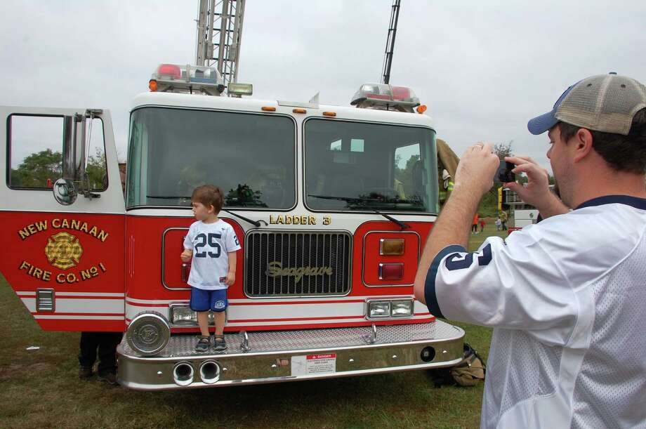 "Michael Stacey photographs son Michael Stacey Jr. in a big fire engine Saturday at Kidzfest Touch-A-Truck. ""I love it,"" he said. ""He loves it."" Photo: Jarret Liotta / Norwalk Citizen contributed"