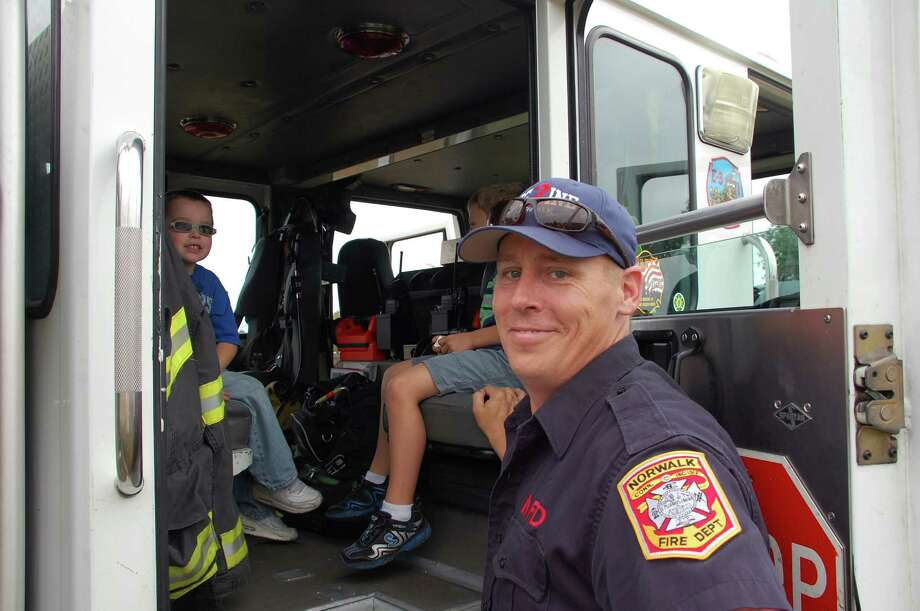 Norwalk Firefighter Jack Kelly helped youngsters get an up close and personal look at a fire engine at Kidzfest Touch-A-Truck fundraiser Saturday. Photo: Jarret Liotta / Norwalk Citizen contributed