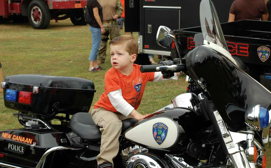 Logan Olive, 2, of Norwalk, tries out a police motorcycle Saturday at Kidzfest Touch-A-Truck. Photo: Jarret Liotta / Norwalk Citizen contributed