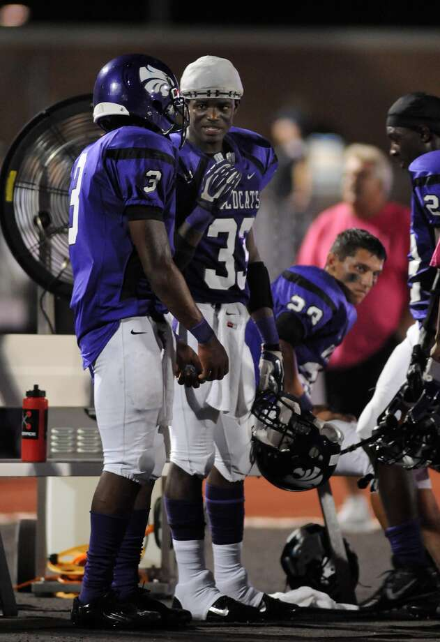 Humble's Edison Williams, from right, and Deneric Gibson talk offensive strategy on the Wildcat bench during their game against Barbers Hill at Turner Stadium. Photo: Jerry Baker, For The Chronicle