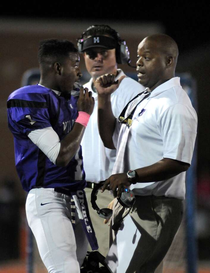 Humble junior quarterback Khalil Berotte, from left, talks offensive strategy with head coach Charles West during their game against Barbers Hill at Turner Stadium. Photo: Jerry Baker, For The Chronicle