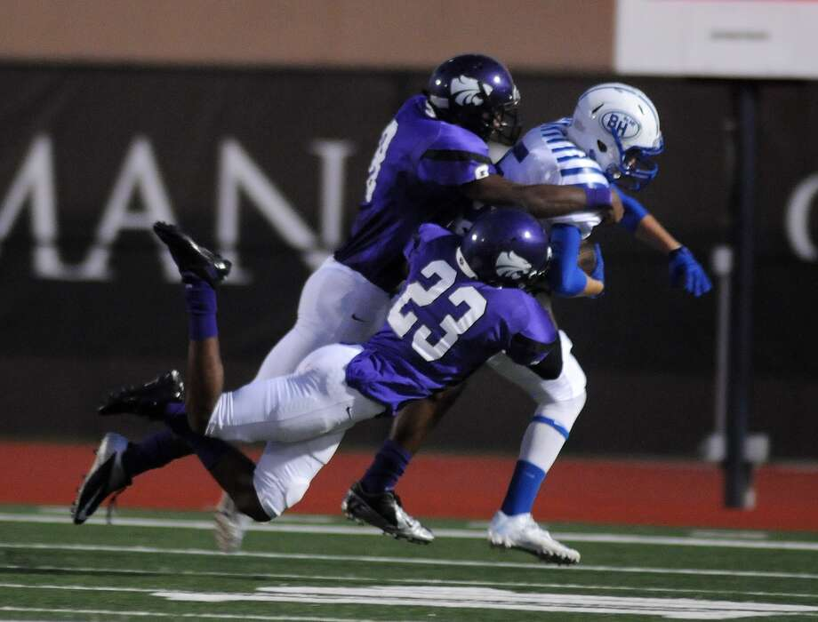 Humble's Kyle Floyd, top, and Brenton Walker (#23) take down Barbers Hill receiver Justin Aaron during their game at Turner Stadium. Photo: Jerry Baker, For The Chronicle