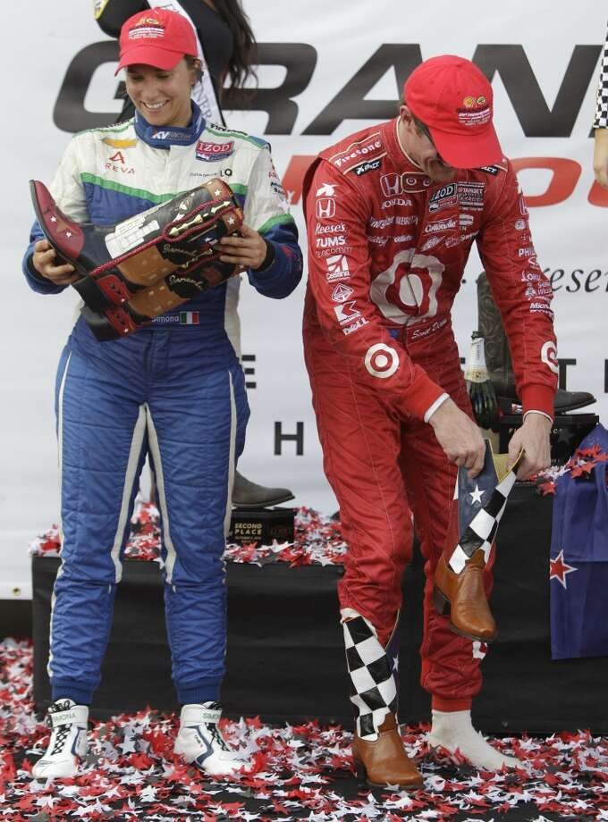 Simona De Silvestro, left, who placed second, and winner Scott Dixon, right, check out their new boots given during awards ceremony after Race 1 on Saturday. Photo: Melissa Phillip, Houston Chronicle