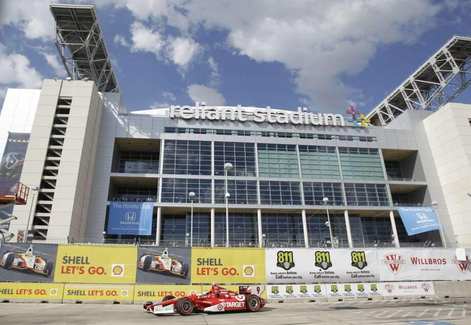 Scott Dixon passes Reliant Stadium during Race 1 of the Shell and Pennzoil Grand Prix of Houston at Reliant Park on Saturday. Dixon won the race. Photo: Melissa Phillip, Houston Chronicle