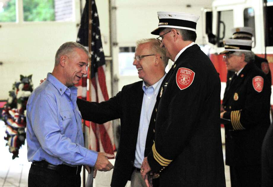 Firefighter Ken Monteavaro receives an award from Danbury Mayor Mark Boughton at the Danbury Fire Department awards ceremony, in Danbury, Conn. Sunday, Oct. 6, 2013 Photo: Michael Duffy