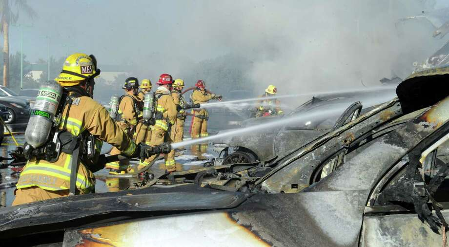 Firefighters respond to a semi crash on the 101 freeway south near Rose Avenue, Saturday, Oct. 5, 2013 in Oxnard, Calif.. Fire officials said one person was transported in a big rig crash and fire that caused about a $1 million in damage at a Carmax in Oxnard Saturday morning.(AP Photo/Ventura County Star, Juan Carlo)  Photo: AP