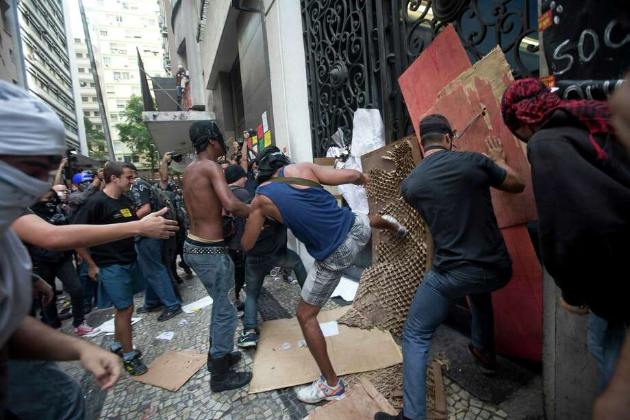 In this Tuesday, Oct. 1, 2013 photo, protestors kick at City Hall's iron gates during a teacher's strike in Rio de Janeiro, Brazil. Teachers opposed to the mayor's proposal to increase teacher's salaries tried to disrupt the proceedings at City Hall. The strikers say the proposal doesn't go far enough to address their demands. Photo: AP