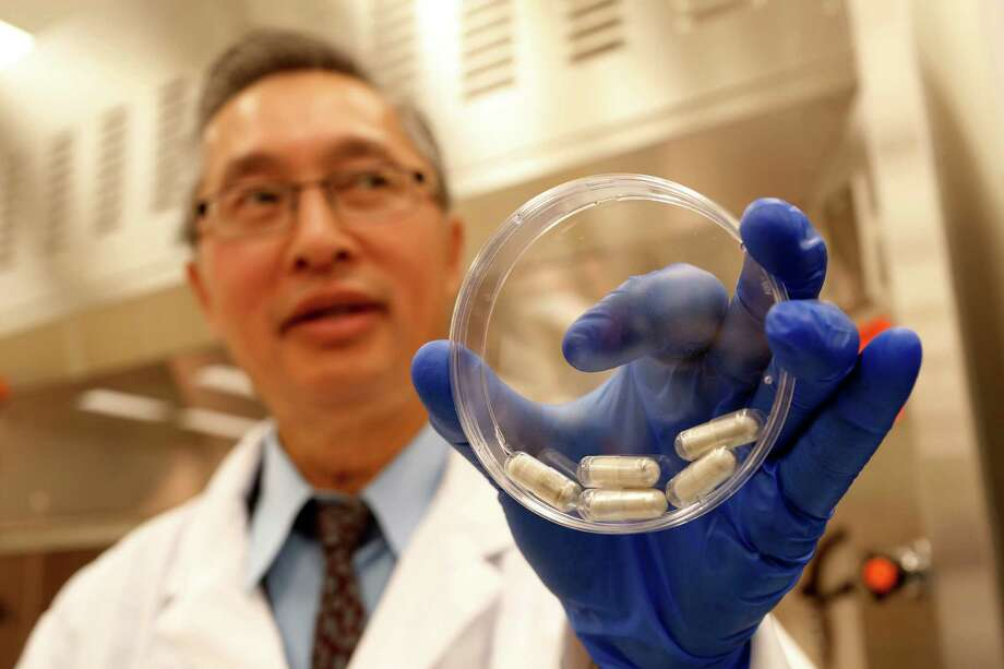 Dr. Thomas Louie, an infectious disease specialist at the University of Calgary, holds a container of stool pills in triple-coated gel capsules in his lab in Calgary, Alberta, Canada on Thursday, Sept. 26, 2013. Half a million Americans get Clostridium difficile, or C-diff, infections each year, and about 14,000 die. A very potent and pricey antibiotic can kill C-diff but also destroys good bacteria that live in the gut, leaving it more susceptible to future infections. Recently, studies have shown that fecal transplants - giving infected people stool from a healthy donor - can restore that balance. Photo: AP