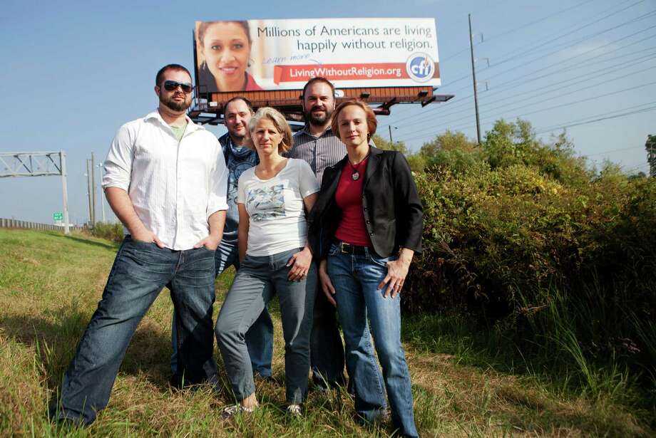 Local members of the Center for Inquiry, from left, Christopher Tanner, Andy Westmoreland, Cathy Seaver, Chip LaFleur, and Jennifer Beahan stand in front of a new billboard along U.S. Route 131-N on Thursday, Oct. 3, 2013. The billboard alongside a highway in western Michigan is spreading the message that religion is something people can live without. (AP Photo/MLive.com, Lauren Petracca) Photo: AP