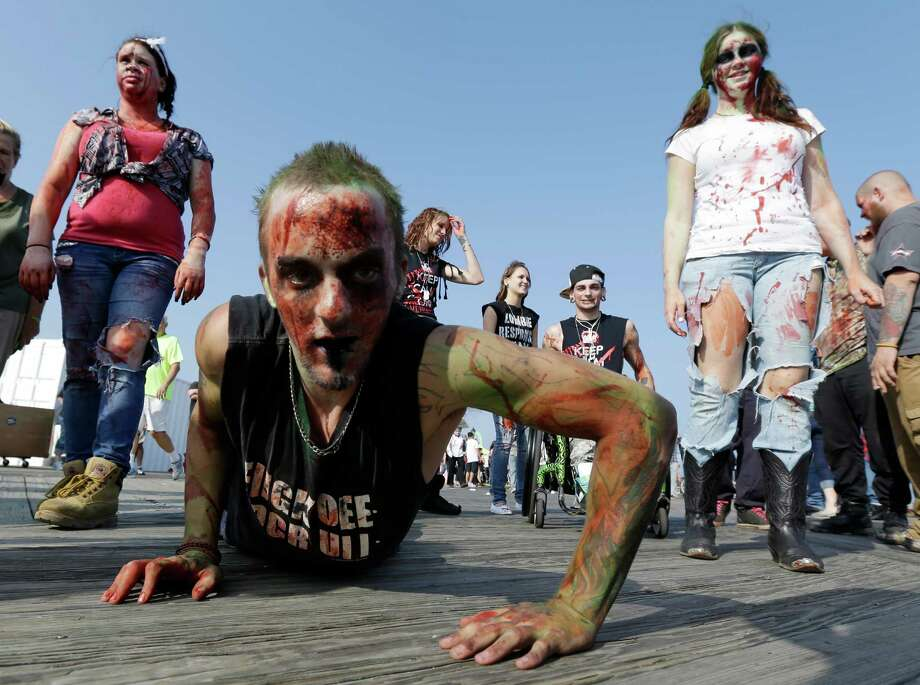 Joe Wiley, of Hamilton, N.J., crawls on the Asbury Park boardwalk during a zombie walk, Saturday, Oct. 5, 2013, in Asbury Park, N.J. According to Guinness World Record adjudicator Michael Empric, the 9,592 zombies gathered sets a new record for largest zombie walk. Photo: AP