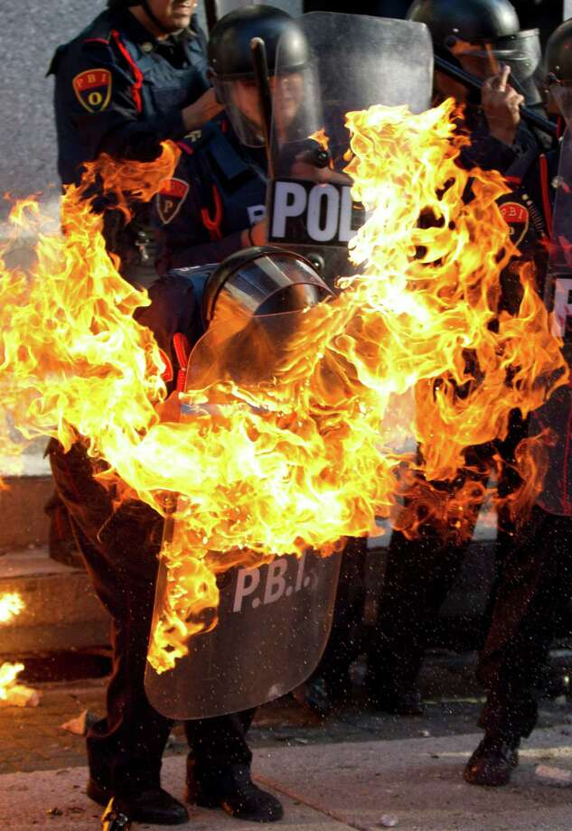 A police officer is engulfed in flames after being hit by a Molotov cocktail thrown by protesters marking the anniversary of the Tlatelolco massacre in Mexico City, Wednesday Oct. 2, 2013. Mexico commemorated the 45th anniversary of the massacre of students holding an anti-government protest, killed by men with guns and soldiers ten days before the 1968 Summer Olympics celebrations in Mexico City. Photo: AP