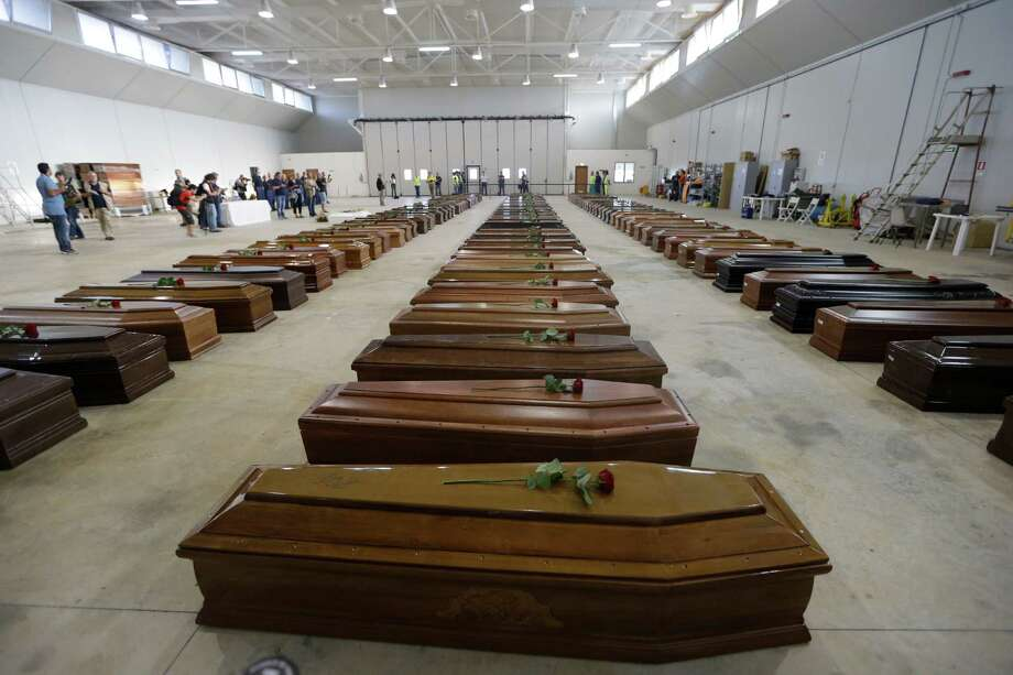 Coffins of the dead migrants are lined up inside an hangar of Lampedusa's airport, Italy, Saturday, Oct. 5, 2013.  A ship carrying African migrants towards Italy sank Thursday after a fire was set onboard to attract attention of any passing boats or people on shore when they ran into trouble. They had traveled for two full days and thought they had reached safety when they saw the lights of Lampedusa. Instead, at least 111 drowned and 155 survived, some of whom were in the water for three hours, clinging to anything buoyant, even empty water bottles. Photo: AP
