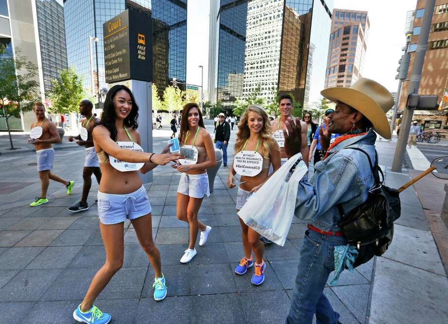 Scantily clad model Katina Shoemaker offers a flyer to a man who declined, saying he has insurance, as Shoemaker and fellow models display signs encouraging the public to get health coverage under the Affordable Care Act, or ACA, during a promotional campaign launched by Colorado HealthOP, a health care co-op, in Denver, Tuesday Oct. 1, 2013. Colorado opened its health exchange marketplace Tuesday after more than two years of planning - but the exchange website temporarily was overwhelmed by tens of thousands of visitors, briefly preventing consumers from creating new accounts. Photo: AP