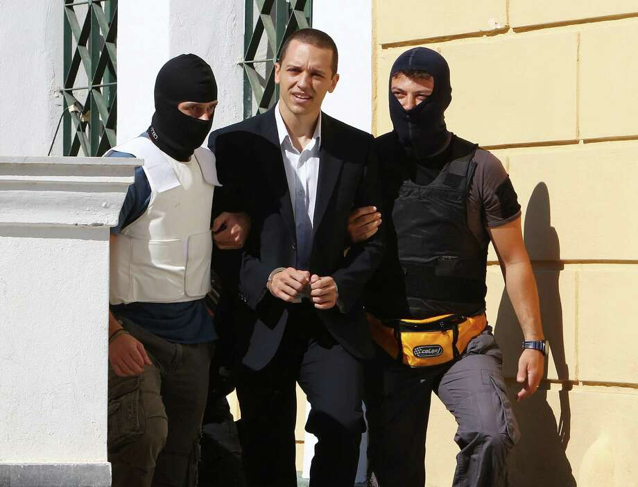 Lawmaker of the extreme far-right Golden Dawn party Ilias Kasidiaris, center, is escorted by anti-terror police to a court for a preliminary hearing into charges of participating in a criminal organization in Athens, Tuesday, Oct. 1, 2013. The party's top leadership, including its leader, are among 22 people arrested in a crackdown on the Nazi-inspired party sparked by the fatal stabbing on Sept. 17 of a Greek rap singer. Photo: AP