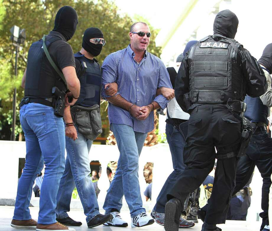 Lawmaker of the extreme far-right Golden Dawn party, Nikos Michos, center, is escorted by anti-terror police to a court for a preliminary hearing into charges of participating in a criminal organization in Athens, Tuesday, Oct. 1, 2013. The party's top leadership, including its leader, are among 22 people arrested in a crackdown on the Nazi-inspired party sparked by the fatal stabbing on Sept. 17 of a Greek rap singer. Photo: AP