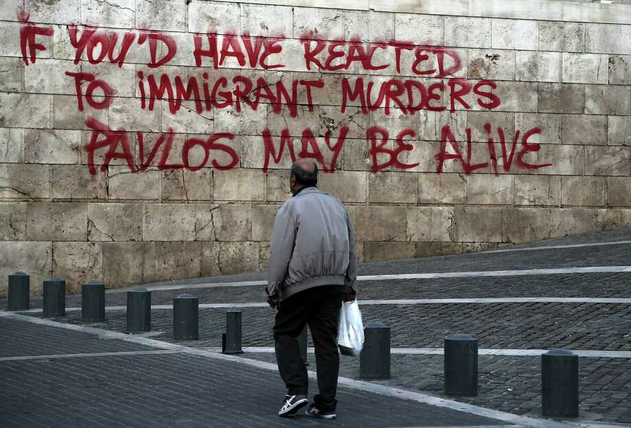 People walk past a graffiti painted on the wall of the Athens' Academy referring to the recent murder of rapper Pavlos Fyssas, allegedly by a member of the far right Golden Dawn party, on Thursday Oct. 3, 2013.  A judge has ordered the detention of Nikos Michaloliakos, the head of Greece's Nazi-inspired Golden Dawn party and one of his lawmakers, Yiannis Lagos, at a maximum-security prison, pending trial on charges of allegedly running a criminal organization. The graffiti accuses that if people had reacted to previous immigrant murders, then murdered rapper Fyssas may still be alive. Photo: AP