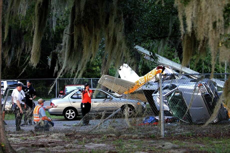 Officials work at the scene of a small plane crash on Flavet Field on the campus of the University of Florida on Saturday, Oct. 5, 2013 in Gainesville, Fla. Two people are hospitalized after a small plane towing a banner crashed near tailgaters gathered for the Florida football game against Arkansas. (AP Photo/The Gainesville Sun, Matt Stamey) Photo: AP