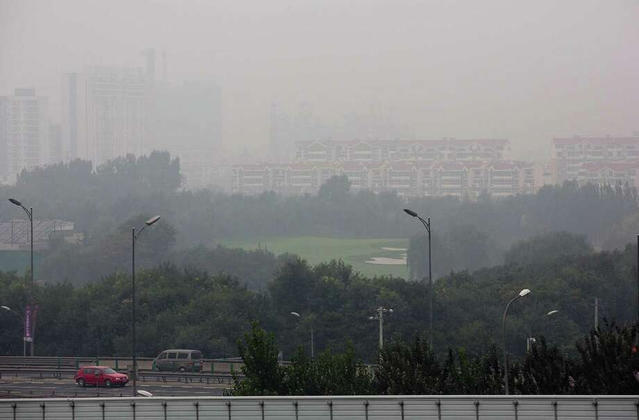 Vehicles drive past residential apartment buildings shrouded by haze in Beijing, China Sunday, Oct. 6, 2013. Fog and pollution descended on northern China on Sunday, leading to flight cancellations and road closures at a time when millions of Chinese were headed home as a weeklong national holiday neared its end. Photo: AP