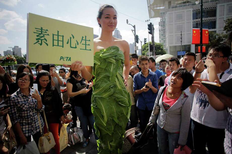 "A member of People for the Ethical Treatment of Animals (PETA) poses in a gown made of lettuce leaves and holds a sign that reads, ""Let Vegetarianism Grow on You"" in Chinese during an event on a busy shopping street in Shanghai, China, Friday, Oct. 4, 2013. According to the organizers, PETA is asking residents to celebrate the Golden Week of the National Day (Oct. 1) by adopting a healthy, kind, and Earth-friendly vegan diet. Photo: AP"