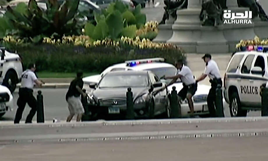This image from video provided by Alhurra Television shows police with guns drawn surrounding a black Infiniti near the U.S. Capitol in Washington, Thursday, Oct. 3, 2013. A woman with a young child inside tried to ram through a White House barricade, then led police on a chase toward the Capitol, where police shot and killed her, witnesses and officials said. Photo: AP
