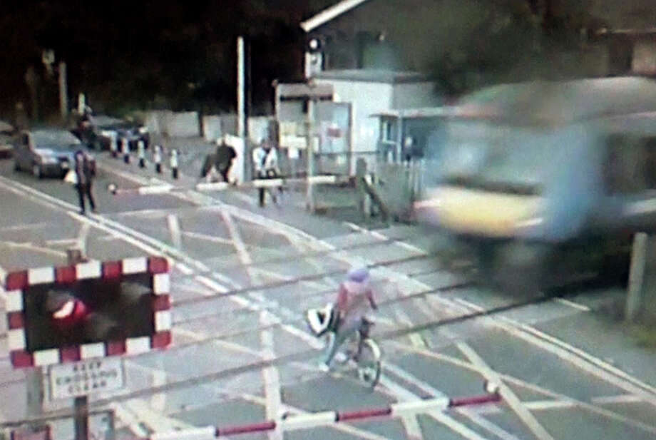 In this still frame made from Sept. 12, 2013, video provided by the British Transport Police, a female cyclist slams on her brakes to avoid being hit by a fast-moving train after she ignored barriers and started to enter a railroad crossing near Waterbeach, north of London. Police said releasing the video Wednesday, Oct. 2, 2013, may make the public more aware of the dangers posed by level train crossings, which are common throughout England. Photo: AP