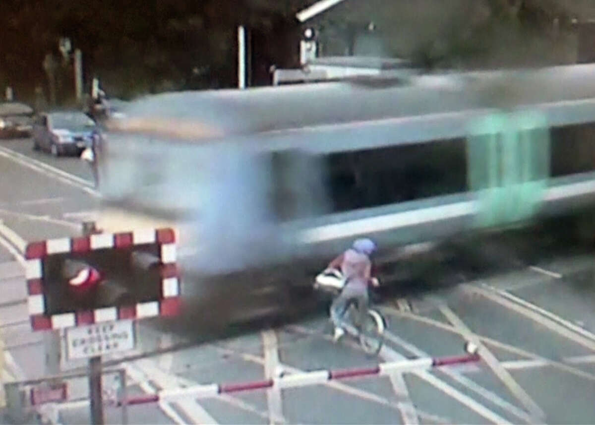 This still frame made from Sept. 12, 2013, video provided by the British Transport Police, shows a female cyclist shortly after she slammed on her brakes to avoid being hit by a fast-moving train near Waterbeach, north of London. The woman ignored barriers and started to enter a railroad crossing seconds before before a train zoomed by. Police said releasing the video Wednesday, Oct. 2, 2013, may make the public more aware of the dangers posed by level train crossings, which are common throughout England.
