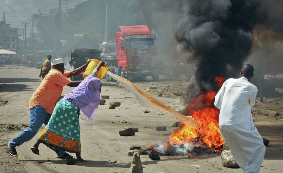 Residents throw water to put out the flames from burning tyres set on fire in a street by rioting youths, following Friday Muslim prayers in Mombasa, Kenya, Friday, Oct. 4, 2013. A religious leader on Kenya's coast says that the Muslim cleric Sheikh Ibrahim Ismael who preached at Mombasa's Masjid Musa Mosque, whose previous imam Aboud Rogo Mohammed was mysteriously shot dead in August 2012, has died in a barrage of bullets late Thursday near the coastal city of Mombasa. Photo: AP