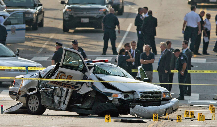 A damaged Capitol Hill police car is surrounded by crime scene tape after a car chase and shooting on Capitol Hill in Washington, Thursday, Oct. 3, 2013. A woman driving a black Infiniti with a young child inside tried to ram through a White House barricade Thursday, then led police on a chase that ended in gunfire outside the Capitol, witnesses and officials said. Photo: AP